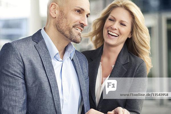 Geschäftsmann und glückliche Geschäftsfrau im Freien