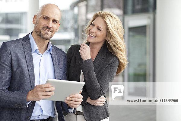 Geschäftsmann und lächelnde Geschäftsfrau mit digitalem Tablett im Freien