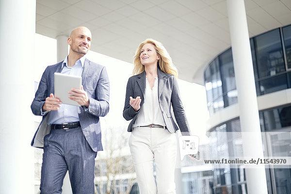 Lächelnder Geschäftsmann und Geschäftsfrau mit digitalem Tablett im Freien