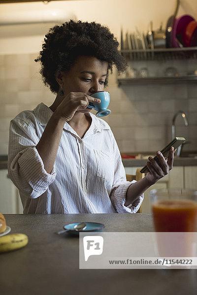 Porträt einer jungen Frau  die in ihrer Küche Espresso trinkt  während sie das Phablet betrachtet.