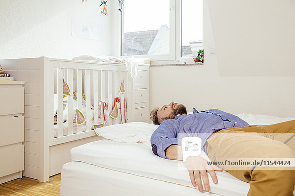 Erschöpfter Vater auf dem Bett liegend