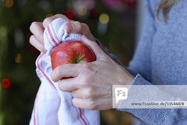 Hand der Frau beim Polieren von Weihnachtsapfel mit Küchentuch  Nahaufnahme Hand der Frau beim Polieren von Weihnachtsapfel mit Küchentuch, Nahaufnahme