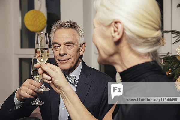 Seniorenpaar klirrt mit Champagner an Silvester