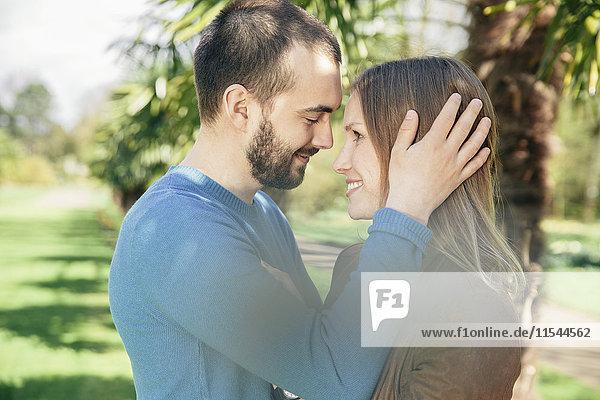 Glückliches Paar von Angesicht zu Angesicht in einem botanischen Garten