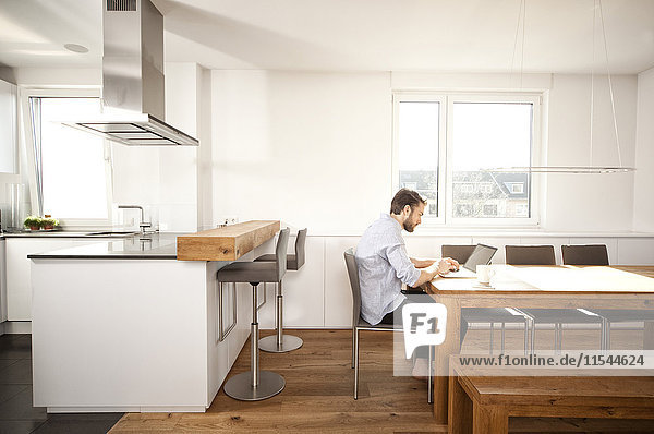 Man sitting at table in his open plan kitchen using laptop