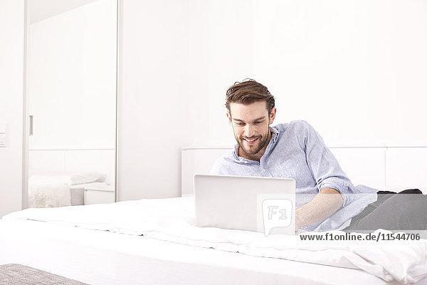 Lächelnder junger Mann auf einem Hotelbett liegend mit Laptop