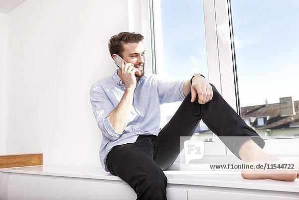 Junger Mann sitzt auf dem Sideboard und telefoniert mit dem Smartphone  während er durchs Fenster schaut.
