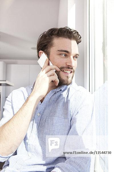 Porträt eines jungen Mannes  der beim Telefonieren mit dem Smartphone durchs Fenster blickt