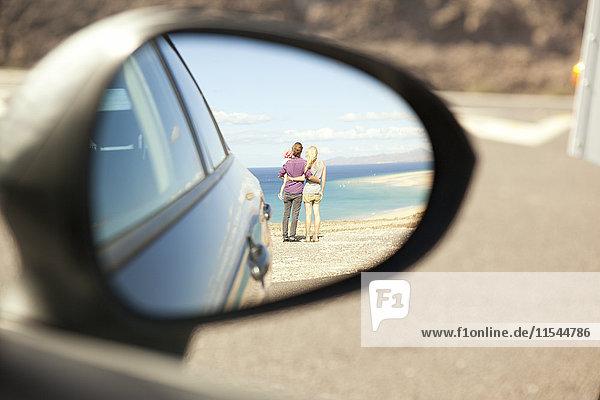 Spanien  Fuerteventura  Jandia  Spiegelung der Familie an der Küste im Außenspiegel eines Autos