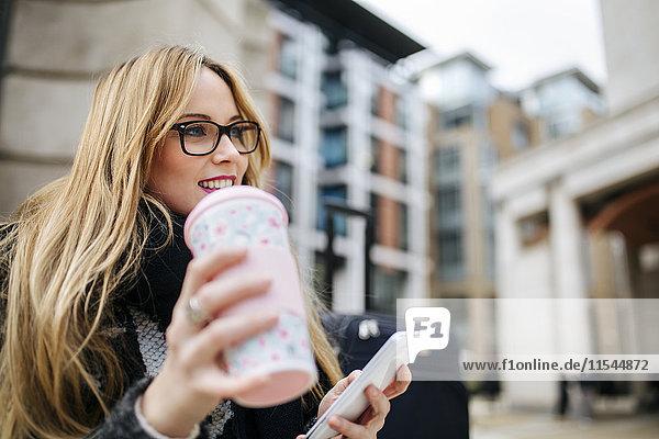 Lächelnde junge Frau mit Kaffee zum Mitnehmen und Handy im Freien