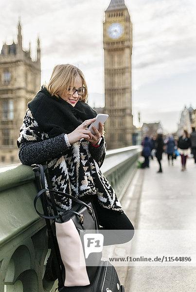 UK  London  junge Frau mit ihrem Smartphone auf der Westminster Bridge