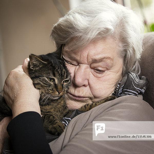 Porträt einer älteren Frau beim Kuscheln mit ihrer Katze