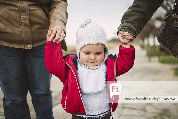 Kleinkind lernt  Hand in Hand mit zwei Frauen zu gehen.