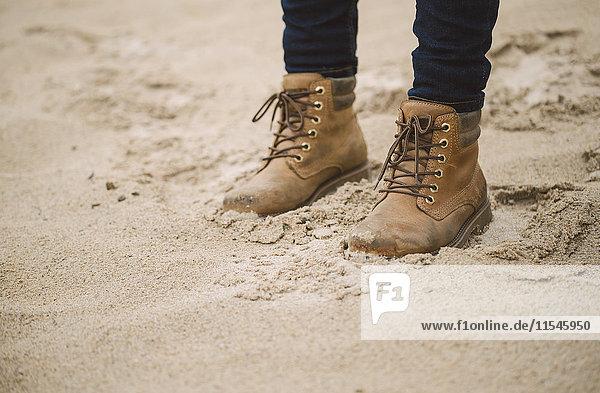 Frau mit im Sand stehenden Robotern  Teilansicht