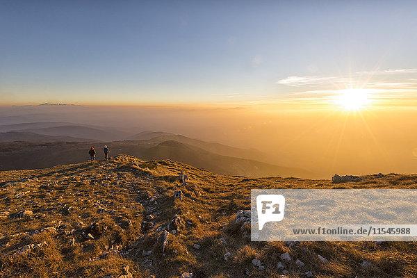 Italien  Marken  Monte San Vicino  zwei Wanderer mit Blick auf den Sonnenuntergang