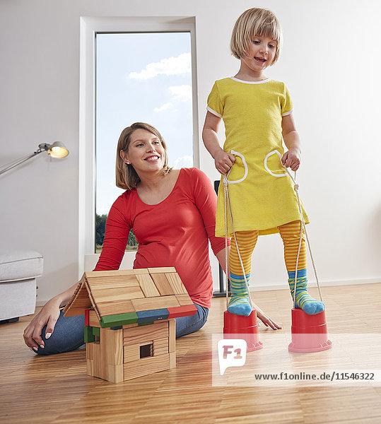 Mutter mit Tochter  die zu Hause auf Eimern läuft.