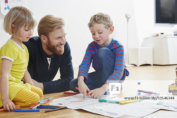Vater auf dem Boden liegend mit Kindermalerei