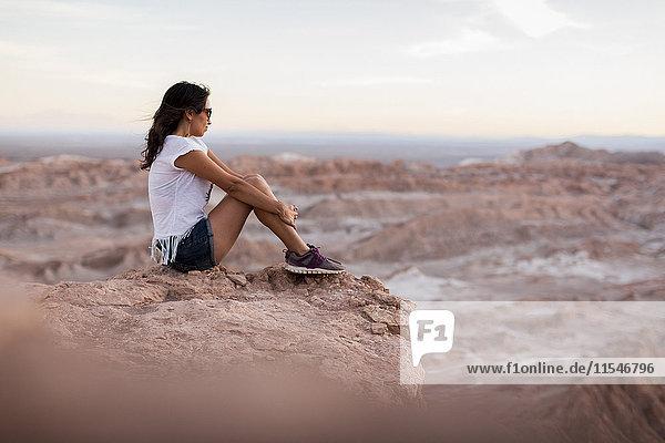 Chile  San Pedro de Atacama  Frau auf Felsen in der Atacama-Wüste sitzend