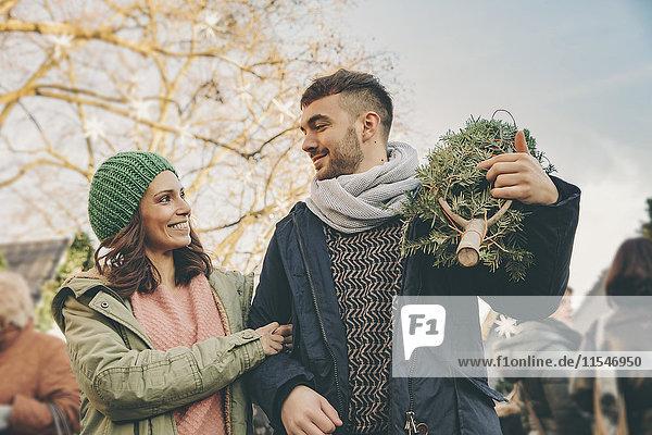 Glückliches Paar mit einem Baum auf dem Weihnachtsmarkt