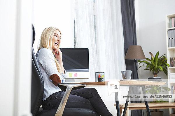 Lachende blonde Frau sitzt am Schreibtisch in ihrem Heimbüro.
