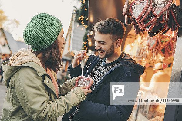 Frau erhält ein Lebkuchenherz von ihrem Freund auf dem Weihnachtsmarkt