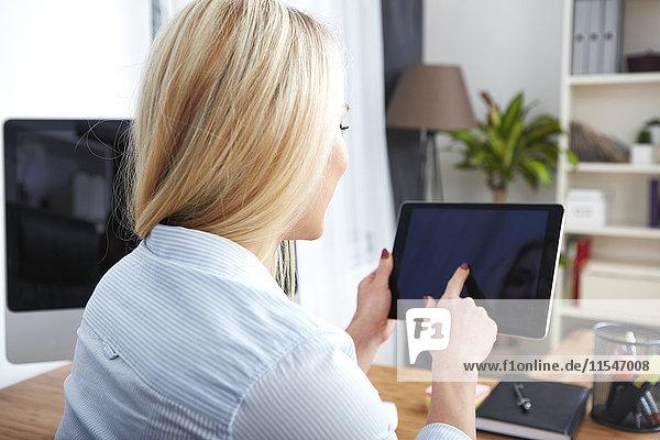 Rückansicht der blonden Frau am Schreibtisch mit digitalem Tablett
