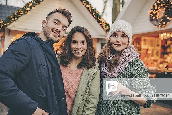 Porträt von drei Freunden auf dem Weihnachtsmarkt