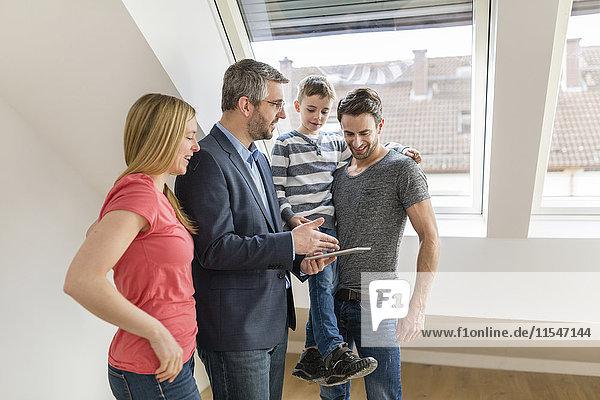 Immobilienmakler eplaining Familie Musterkarte in ihrem neuen Penthouse