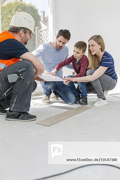 Bauarbeiter zeigt Familienfliesenmuster