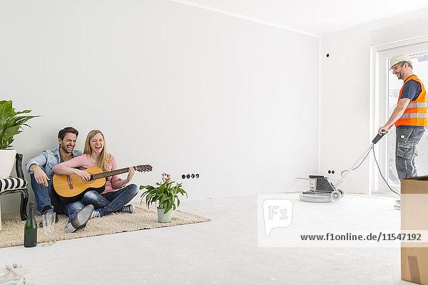 Ein glückliches Paar spielt Gitarre und singt in ihrem neuen Zuhause.