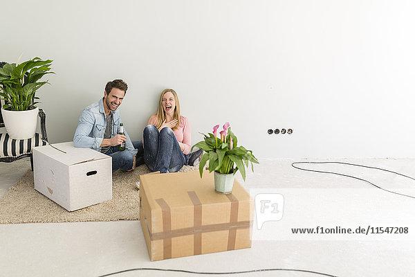 Ein glückliches Paar sitzt auf dem Boden ihres unfertigen neuen Heims