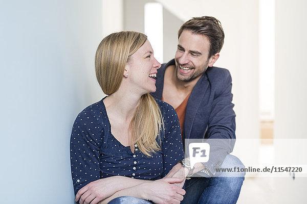 Lachendes Paar hält sich in seiner neuen Eigentumswohnung an den Händen