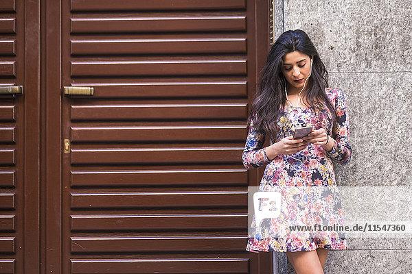 Junge Frau mit gegen die Fassade gelehnten Kopfhörern beim Blick auf ihr Smartphone Junge Frau mit gegen die Fassade gelehnten Kopfhörern beim Blick auf ihr Smartphone