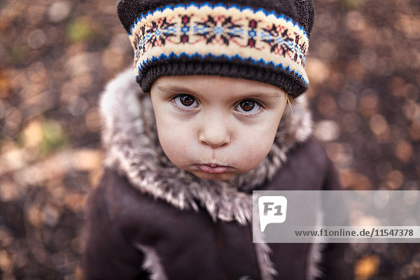 Portrait of pouting little girl in autumn