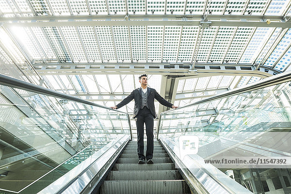 Jungunternehmer auf einer Rolltreppe stehend