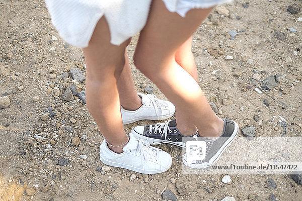 Beine von zwei jungen Frauen in Turnschuhen Beine von zwei jungen Frauen in Turnschuhen
