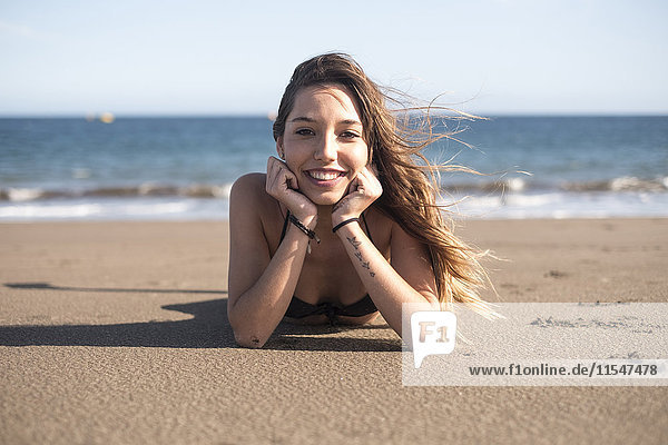 Spain  Tenerife  portrait of young woman relaxing on the beach