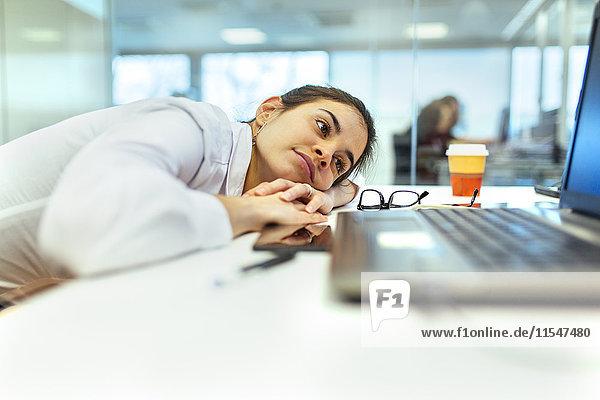 Junge Frau langweilig an ihrem Schreibtisch im Büro