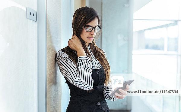 Junge Geschäftsfrau beim Blick auf ihr Smartphone