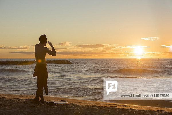 Rückansicht des Surfers  der am Strand steht und den Sonnenaufgang beobachtet.