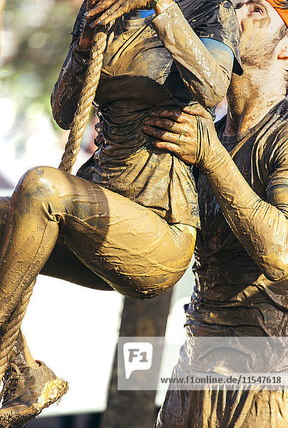 Participant in extreme obstacle race climbing up a rope with assistance of man
