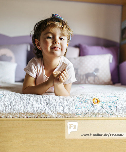Porträt eines kleinen Mädchens auf dem Bett liegend