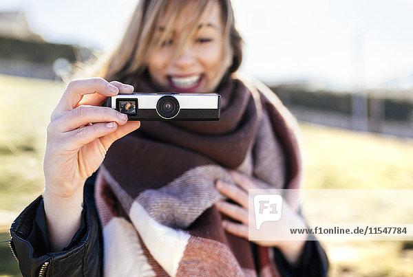 Frau beim Fotografieren mit einer antiken Kamera
