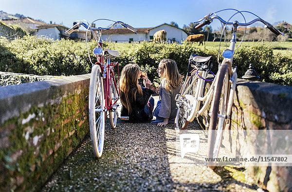 Zwei junge Frauen mit Fahrrädern  die draußen Äpfel essen. Zwei junge Frauen mit Fahrrädern, die draußen Äpfel essen.