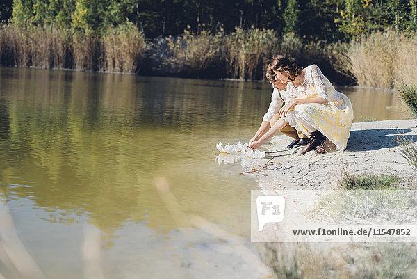 Liebende kauern Seite an Seite an der Wasserseite