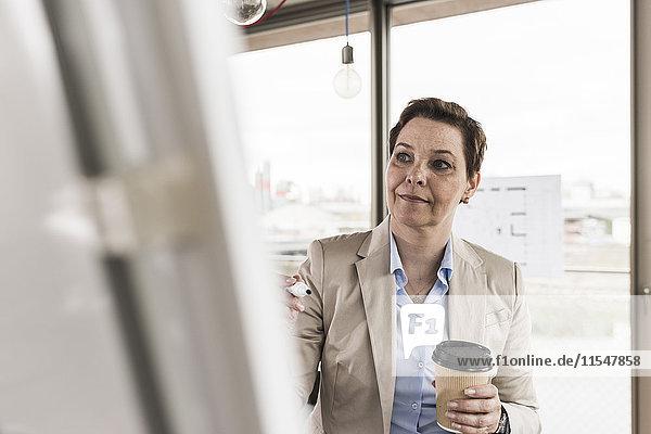 Geschäftsfrau beim Blick auf Flipchart