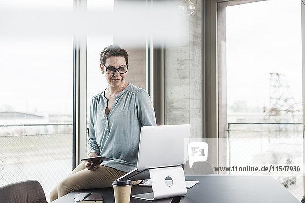 Geschäftsfrau mit Laptop und digitalem Tablett im Büro