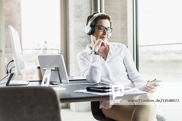 Geschäftsfrau mit Handy und Kopfhörer im Büro