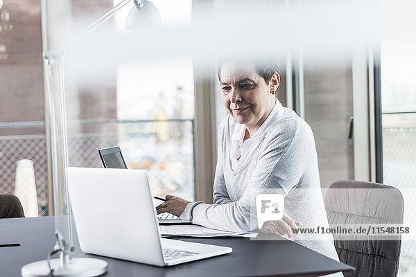 Lächelnde Geschäftsfrau am Schreibtisch mit Blick auf den Laptop