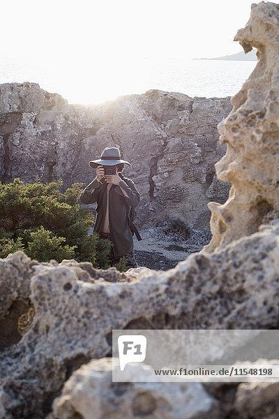 Spanien  Ibiza  Fotograf in Felsen stehend mit Diskettenhut beim Fotografieren